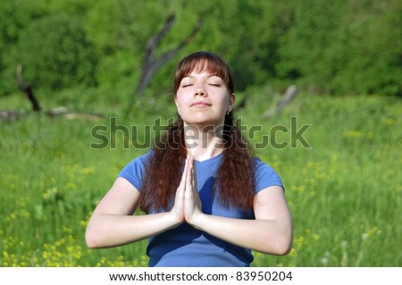 Young happy woman training yoga on green meadow - stock photo
