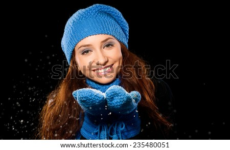 Young happy woman under snowfall, isolated over black - stock photo