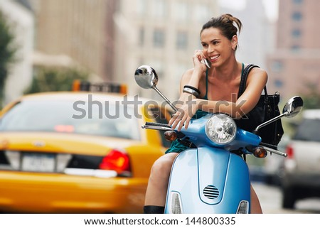 Young happy woman using mobile phone on moped - stock photo