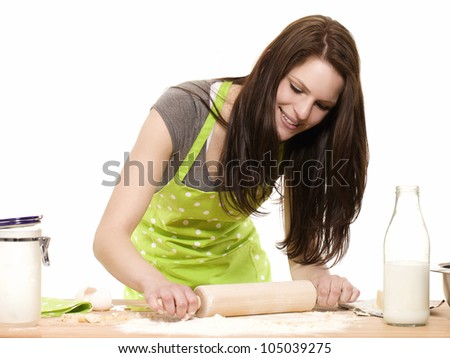young happy woman using rolling pin on dough with white background - stock photo