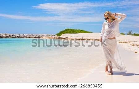 Young happy woman walking on the beach - stock photo