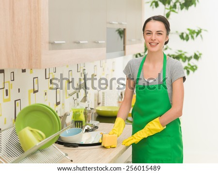 young happy woman washing dishes at home - stock photo