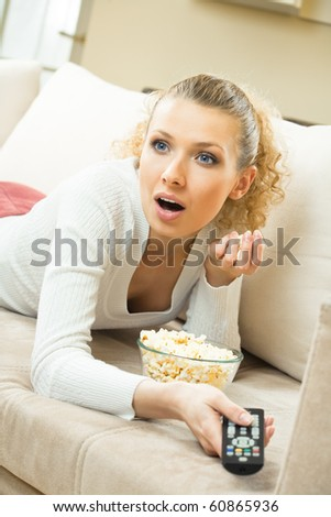 Young happy woman watching TV at home - stock photo