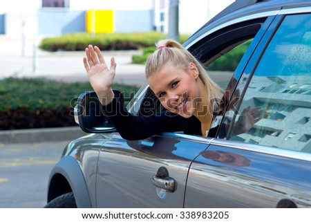 Young happy woman waving through a car window - stock photo