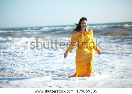 Young happy woman wearing yellow dress walking at the coastline - stock photo