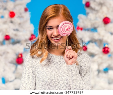 Young happy woman with a big candy during the celebration of Christmas, Christmas tree background