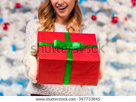 Young happy woman with a box for a gift, during the celebration of Christmas, Christmas tree background - stock photo