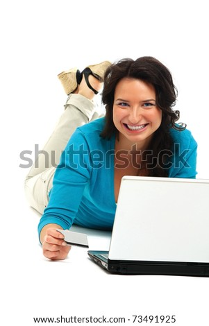 Young happy woman with a laptop lying on the floor - stock photo
