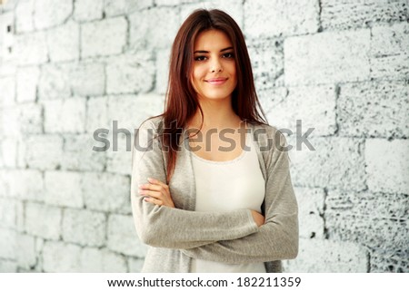Young happy woman with arms folded standing near brick wall - stock photo