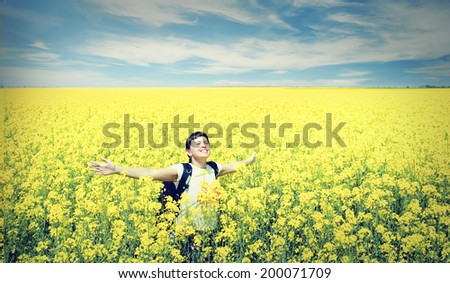 Young happy woman with backpack on a field of yellow rape - stock photo