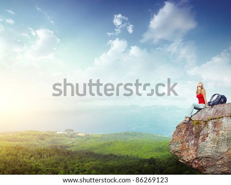 Young happy woman with backpack sitting on a cliff's edge - stock photo