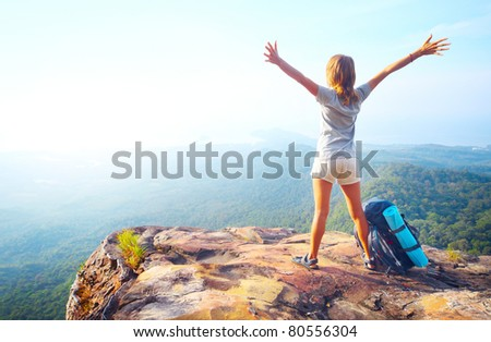 Young happy woman with backpack standing on a rock with raised hands and looking to a valley below - stock photo