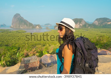 Young happy woman  with backpack standing on top of the mountain and enjoying valley view