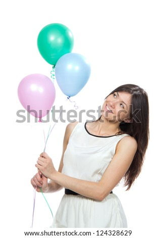 Young happy woman with balloons as a present for birthday party smiling and looking at the corner on a white background - stock photo