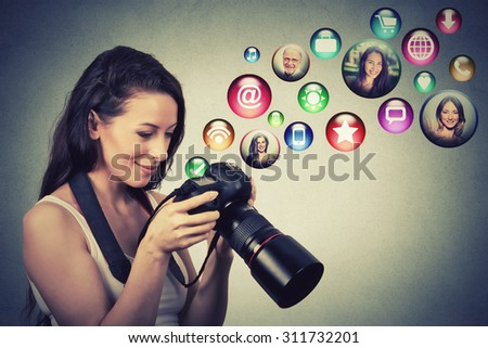 Young happy woman with camera models social media icons flying out of screen isolated on gray wall background