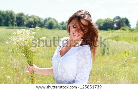 Young happy woman with chamomile bouquet - stock photo