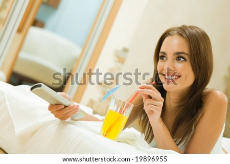 Young happy woman with cocktail watching TV at bedroom - stock photo