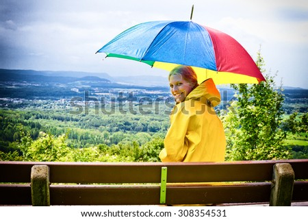 Young happy woman with colorful umbrella - stock photo