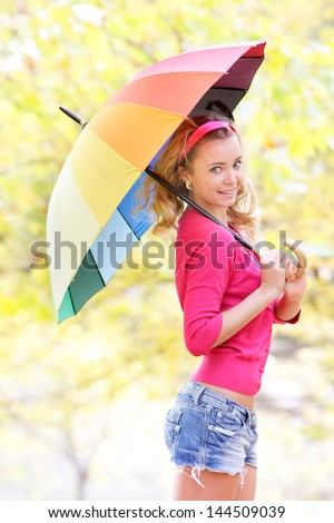 young happy woman with colorful umbrella in autumn park