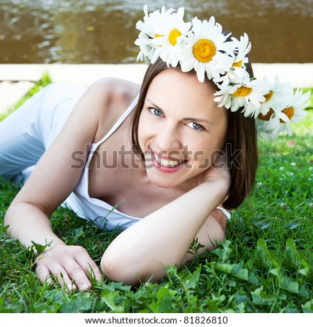 Young happy woman with daisy crown on head relaxing outdoors