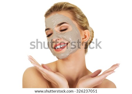 Young happy woman with facial mask, isolated on white. - stock photo