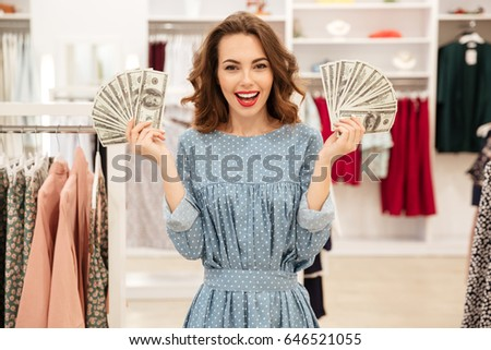 Young happy woman with fans of money looking camera in clothing store