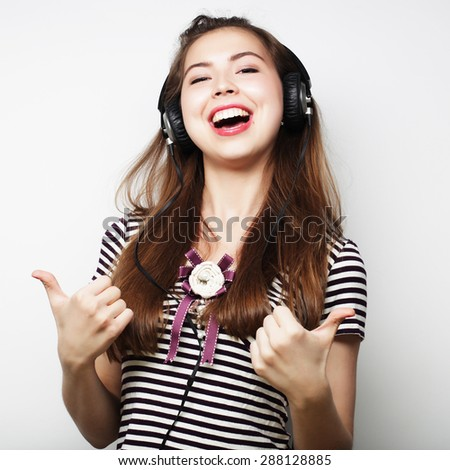 Young happy woman with headphones listening music over grey background - stock photo