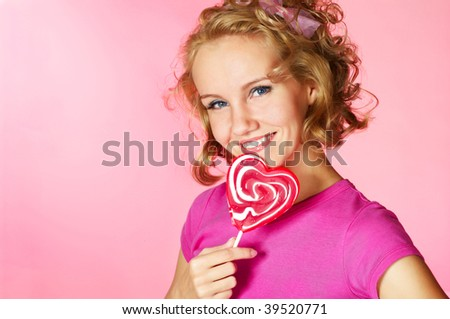 young happy woman with heart shaped lollipop; closeup face - stock photo
