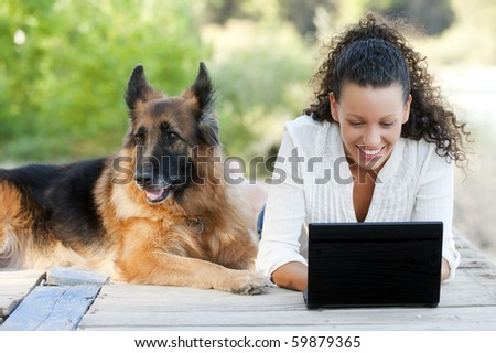 Young happy woman with her dog and laptop - stock photo