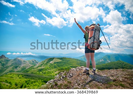 Young happy woman with hiking stick, backpack standing on the rock with raised hands and looking to green lanscape  - stock photo