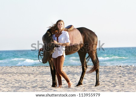 young happy woman with horse on sea background - stock photo