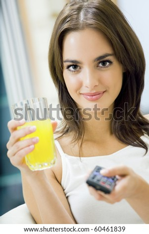 Young happy woman with juice, watching TV at home - stock photo