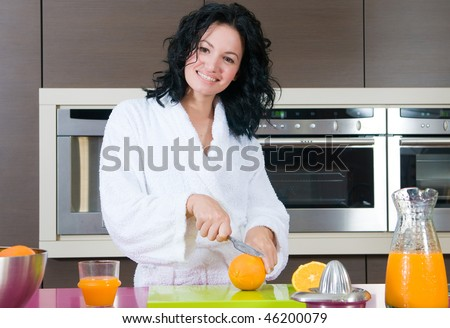 Young happy woman with orange juice at domestic kitchen