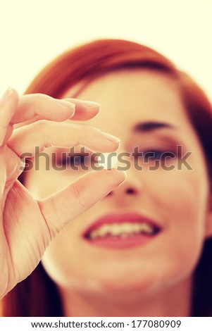 Young happy woman with pill, isolated  - stock photo