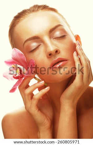 young happy woman with pink orchid, studio shot - stock photo