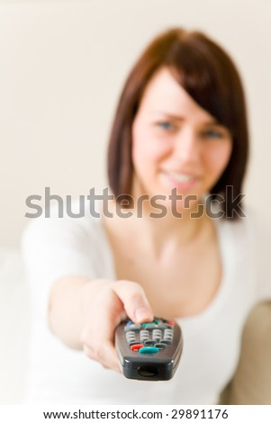 Young happy woman with remote control on a sofa in her living room
