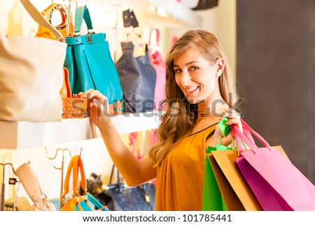 Young happy woman with shopping bags having fun while shopping in a mall - stock photo