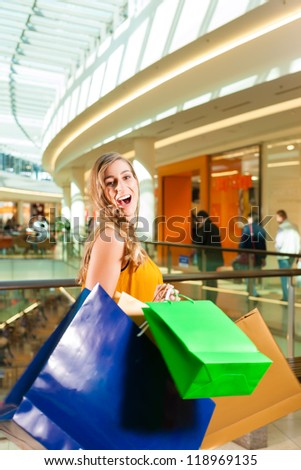 Young happy woman with shopping bags having fun while shopping in a mall