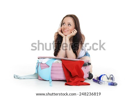 Young happy woman with suitcase sits on a white background. Vacation. - stock photo