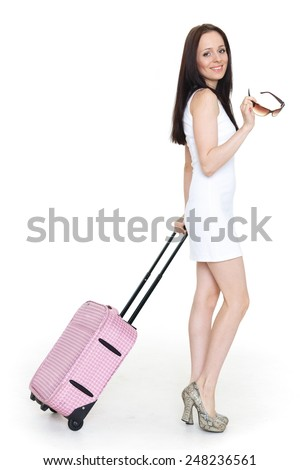 Young happy woman with suitcase stands on a white background. Vacation. - stock photo