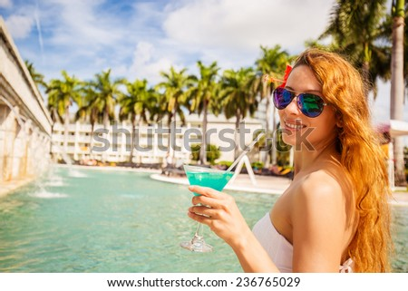 Young happy woman with sunglasses holding cocktail enjoying sunny weather seating by resort swimming pool outdoors. Tropical paradise getaway travel vacation tourism concept. Positive face expression - stock photo