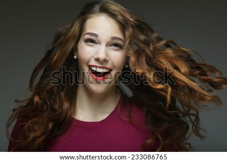 Young happy woman with wind in hair. Studio shot.