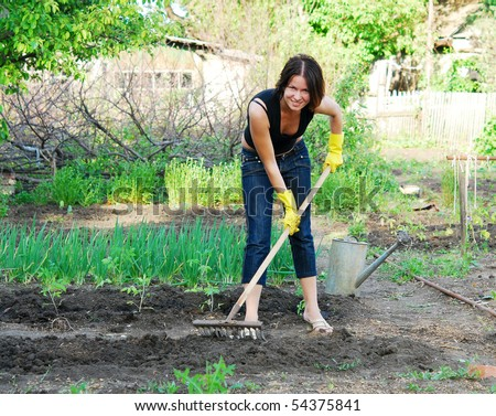 young happy woman working in the garden - stock photo