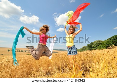 young happy women on field in summer