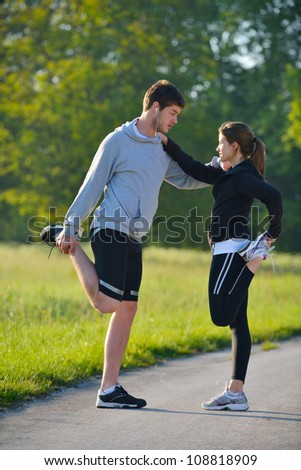 young health couple doing stretching exercise relaxing and warm up after jogging and running in park - stock photo