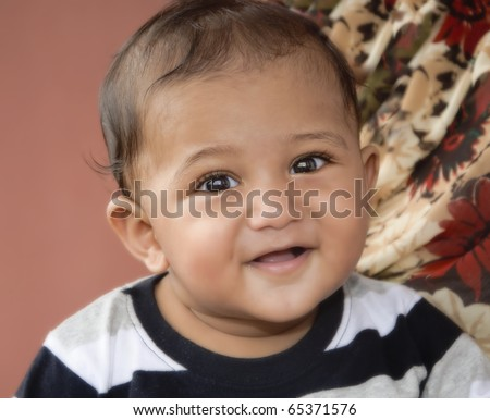 Young health Indian origin Asian toddler smiling at the camera - stock photo