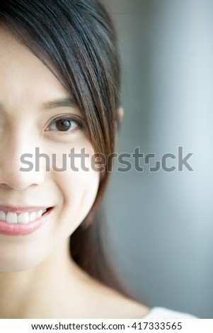 young health woman smile to you. half face, with health teeth and skin, asian beauty - stock photo
