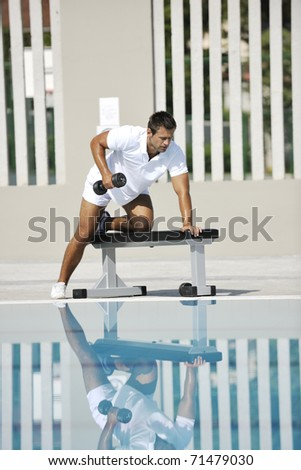young healthy athlete man exercise at poolside - stock photo