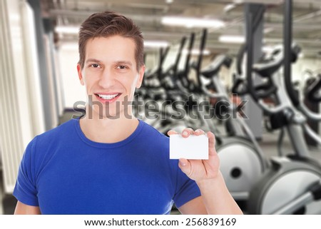 Young Healthy Athletic Man Holding Blank Visiting Card At Gym - stock photo