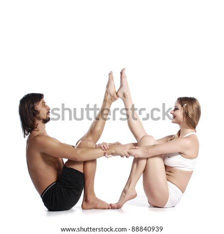 Young healthy couple in yoga position on white background - stock photo